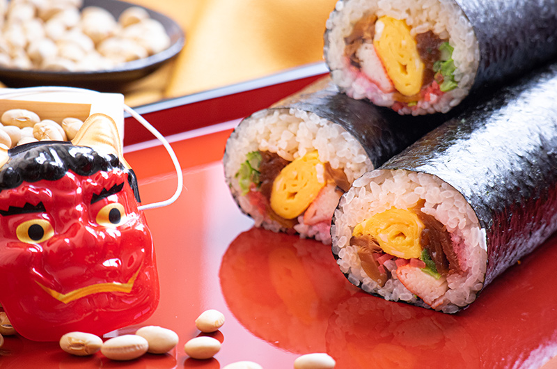 Japanese traditions for setsubun. Sushi, demon masks, and beans.