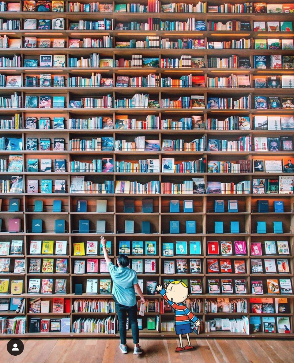The wall of books at Hirakata T-site is so tall! Osaka Bob and his friend have to stretch to reach the cover they want.